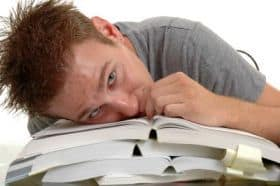 Man with his head lead on books -Eexam stress
